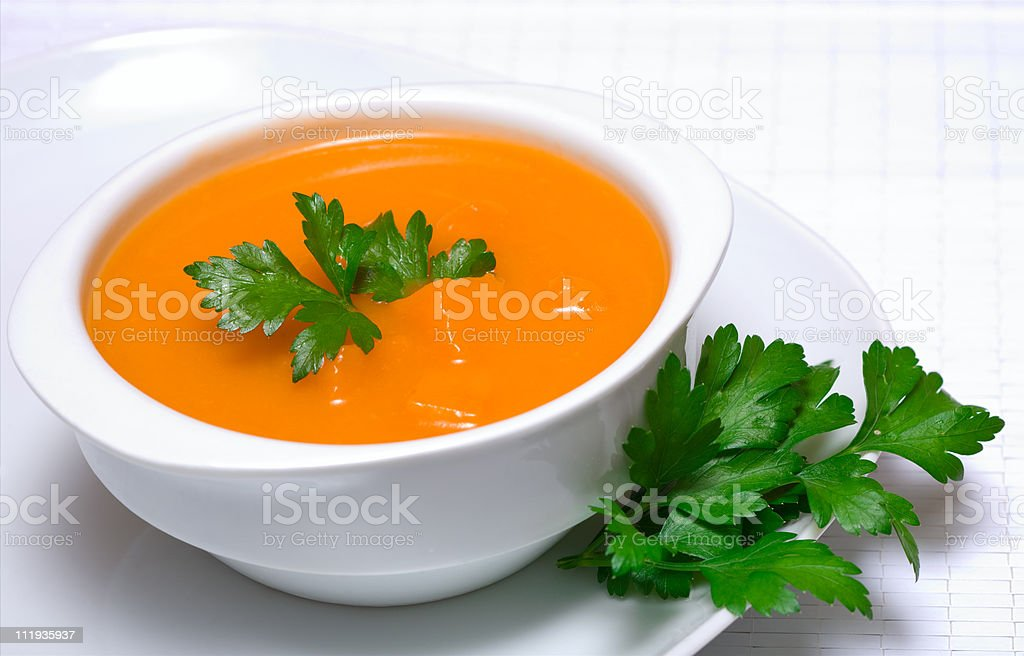 Pumpkin soup in white bowl  with parsley stock photo