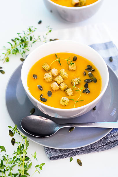 pumpkin soup served with croutons and pumpkin seeds - mash food state stock photos and pictures
