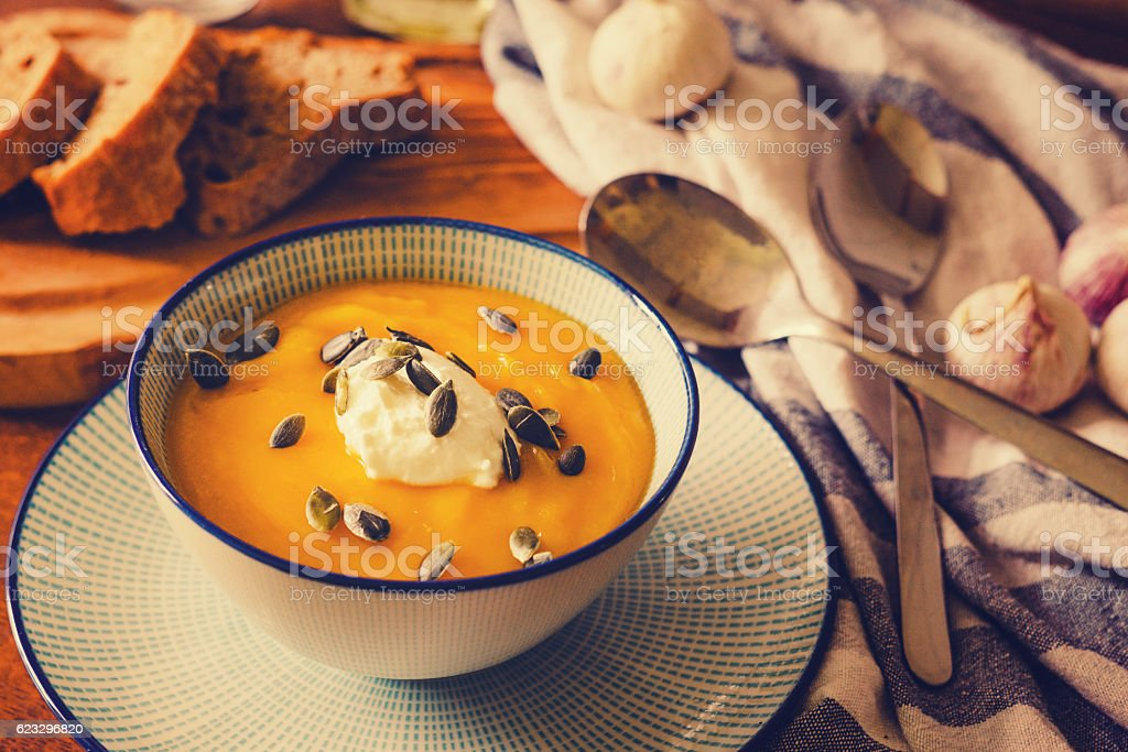Pumpkin soup served with sour cream and pumpkin seeds stock photo