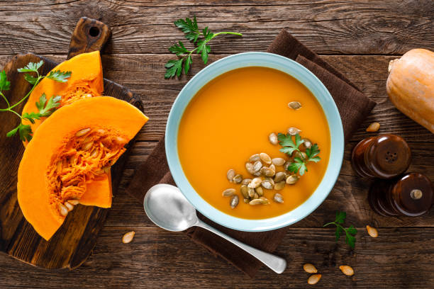 Pumpkin soup. Vegetarian soup with pumpkin seeds in bowl on wooden table, top view stock photo
