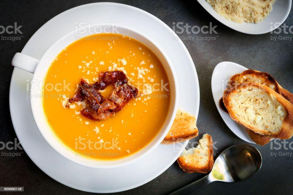 Pumpkin Soup with Bacon Parmesan and Garlic Bread Top View stock photo