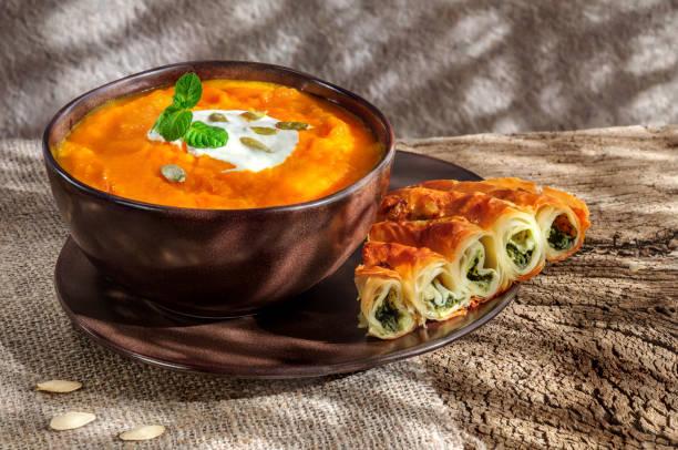 pumpkin soup with cream and spanich pie on dark wooden background - pumpkin pie стоковые фото и изображения