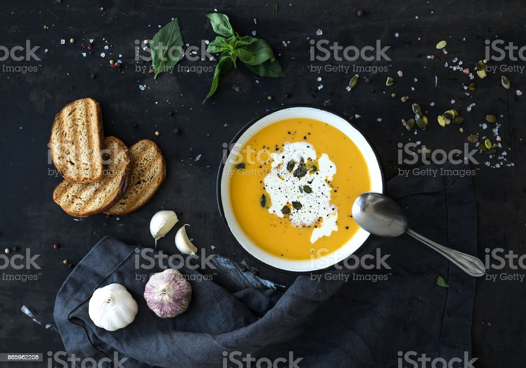 Pumpkin soup with cream, seeds, bread and fresh basil on grunge black background stock photo