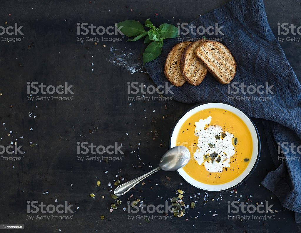 Pumpkin soup with cream, seeds, bread and fresh basil on