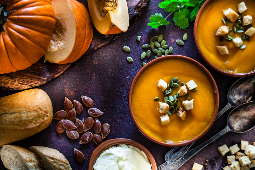 Pumpkin soup with ingredients on rustic brown table. Top view