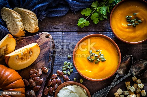 Two brown bowls filled with homemade pumpkin soup surrounded by ingredients for preparing soup shot from above on rustic wooden table. Predominant colors are orange and brown. Low key DSRL studio photo taken with Canon EOS 5D Mk II and Canon EF 100mm f/2.8L Macro IS USM.