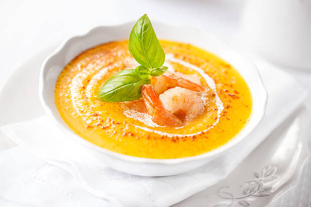 Pumpkin soup with shrimps and basil stock photo