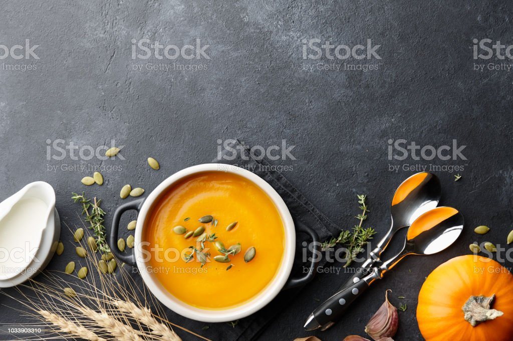 Pumpkin soup with thyme and pumpkin seeds on black background royalty-free stock photo