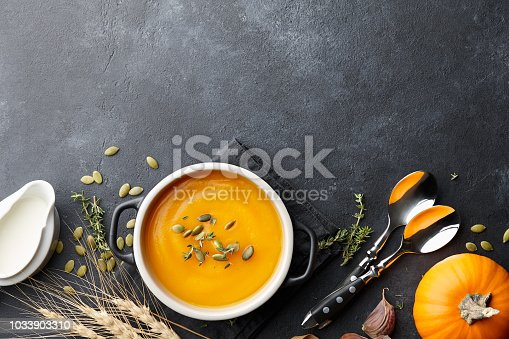 Pumpkin soup with thyme herb, cream and pumpkin seeds served in black bowl, top view