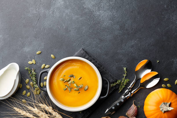 Pumpkin soup with thyme and pumpkin seeds on black background Pumpkin soup with thyme herb, cream and pumpkin seeds served in black bowl, top view squash vegetable stock pictures, royalty-free photos & images