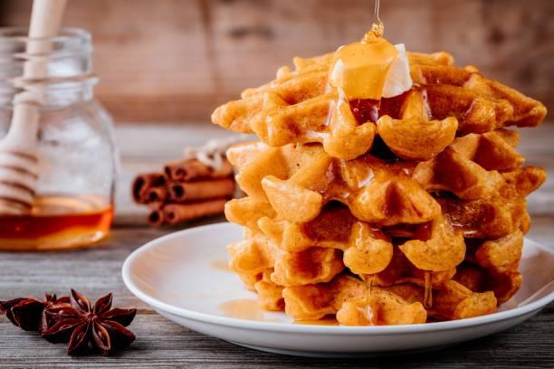 kürbis gewürz waffeln mit butter und honig zum erntedankfest. - zimt waffeln stock-fotos und bilder
