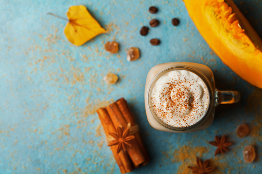 istock Pumpkin spiced latte or coffee in cup decorated cinnamon on turquoise vintage table top view. Autumn, fall or winter hot drink. 840173902