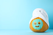 istock Pumpkin with facial mask and towel on blue background, copy space 1178964331