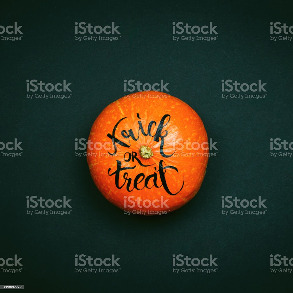 Pumpkin with hand lettered sign Trick or Treat. Halloween concept. stock photo