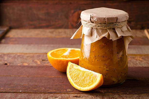 pumpkin-orange-ginger-poppy seed jam on wooden background. - ingwermarmelade stock-fotos und bilder