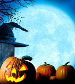 A group of pumpkins and a jack o'lantern rest in the grass in front of a large full moon that rises in the background framed by the bare branches of a tree.  A witch's hat sits on a fence behind the jack o' lantern.