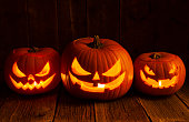 Pumpkins carved for Halloween on Rough Wood Table.