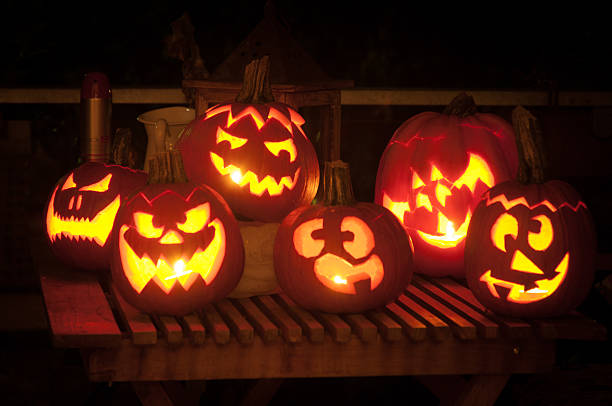 Pumpkins cut into Jack O' Lanterns with candles inside stock photo