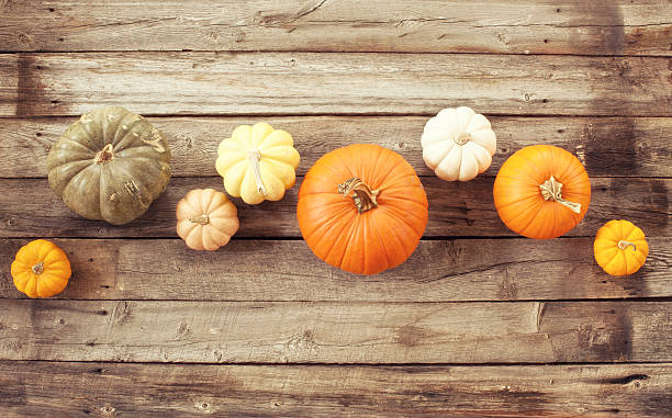 Pumpkins Gourds And Autumn Leaves On Old Wood Background Stock Photo