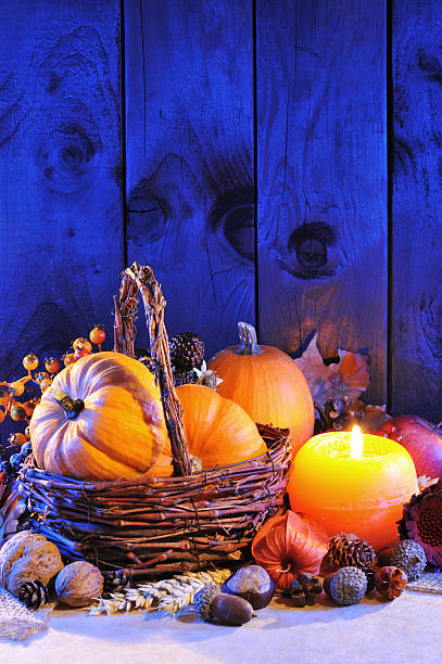 pumpkins in candle light Thanksgiving - different pumpkins, nuts, maize cob and apple in rattan basket with candlelight in blue sunset light anhydrous stock pictures, royalty-free photos & images