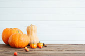 Pumpkins on a wooden table against white wooden wall Organic food and healthy food concept Thanksgiving and Halloween concept.