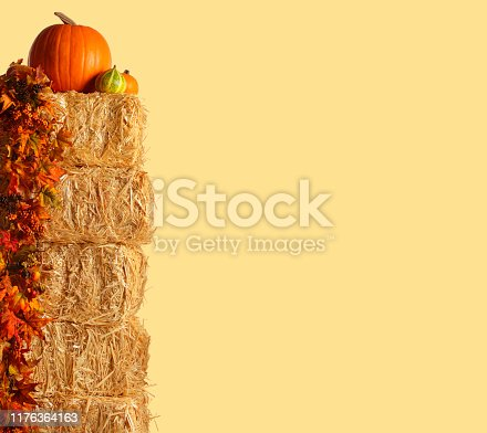 A group of pumpkins rest on top of a stack of hay bales that are adorned with a garland of fall leaves isolated against a pale yellow background.