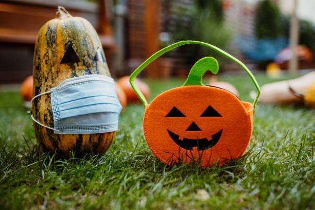 calabazas en la hierba con máscara protectora de rostro durante la pandemia de covid-19 - halloween covid fotografías e imágenes de stock