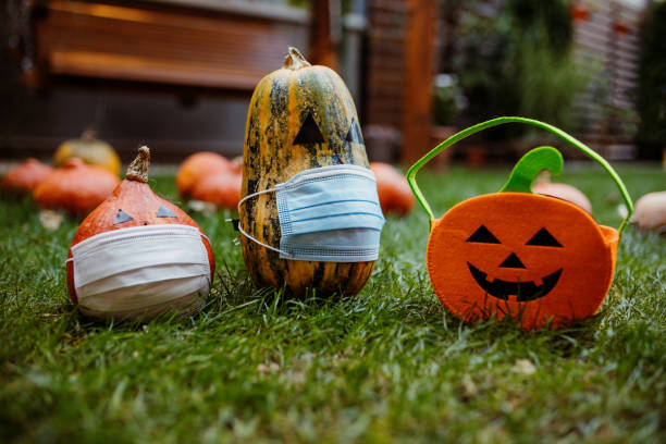 Pumpkins on the grass with face protective mask during Covid-19 pandemic stock photo