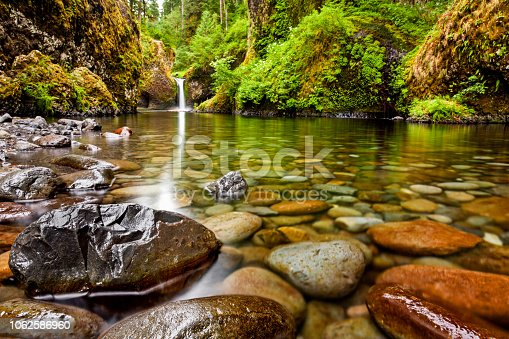 Punch Bowl Falls along the Eagle Creek Trail in Oregon with focus on the rocks in the foreground