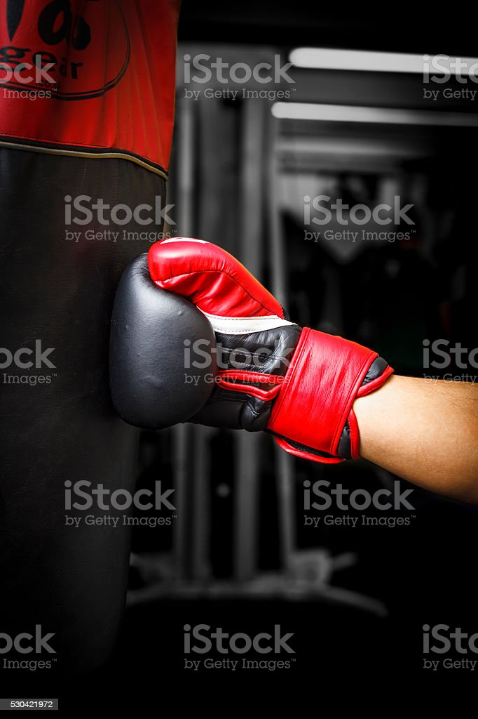 Punching a punching bag with red boxing gloves stock photo