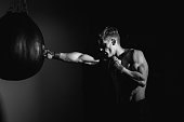 Image of a athletic young adult man punching bags with boxing gloves on. Horizontal composition, with backlight toned to black and white in post processing. This young man is working out, and this image could be used in many athletic sport types of media. Staying physically active is an important part to staying healthy. This young man takes care of his body by giving it the exercise it deserves.