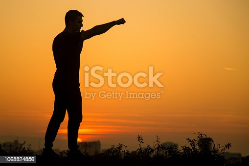 Silhouette of a unrecognizable young man punching.