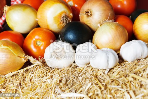 Mixed fresh vegetables resting on straw in a farmers market include the important - if pungent - flavourants of garlic and onions, along with juicy tomatoes.