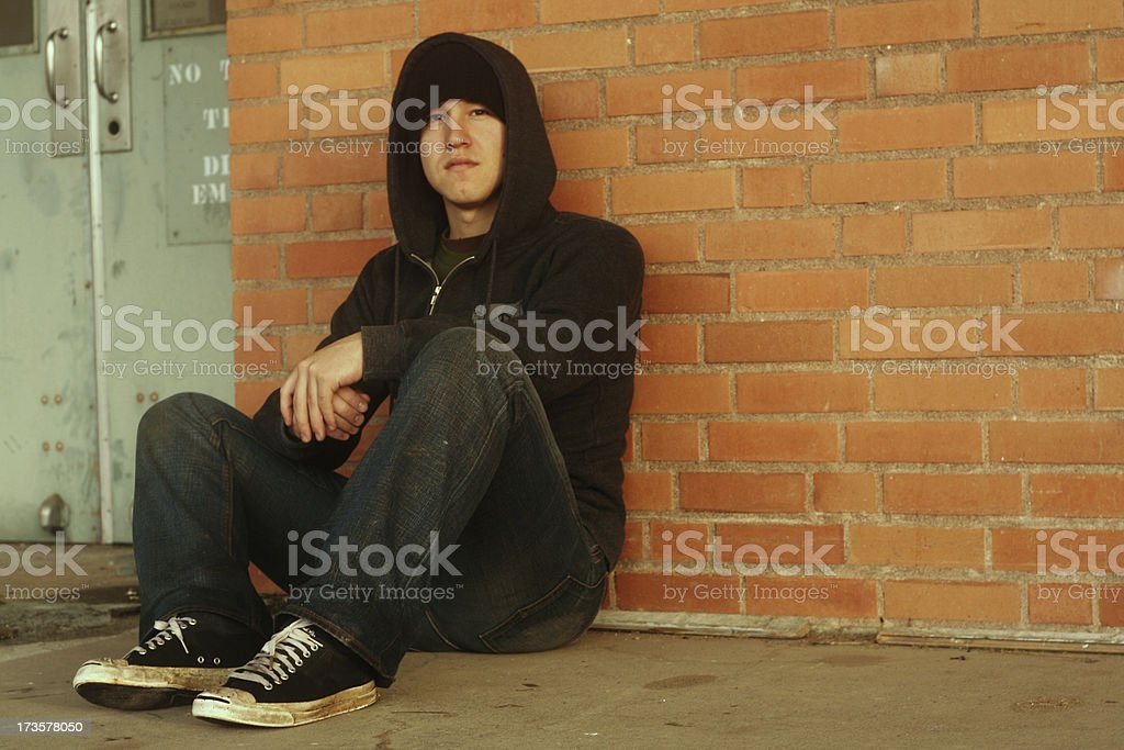 Punk and a hoodie with dirty shoes sitting by brick wall stock photo