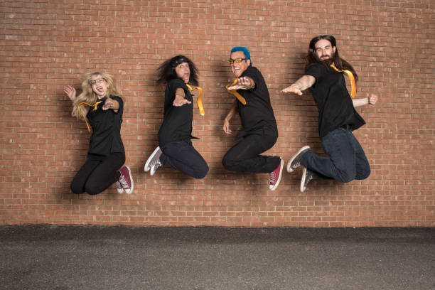 punk band jumping against brick wall - punk music stock photos and pictures