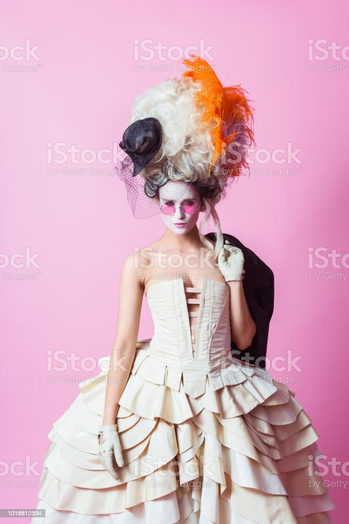 Punk baroque style woman wearing big wig, pink backgroud stock photo