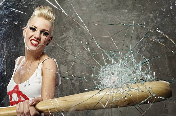 Punk girl breaking glass with a bat stock photo