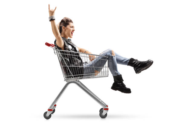 punk girl riding in shopping cart and making rock gesture - punk music stock photos and pictures