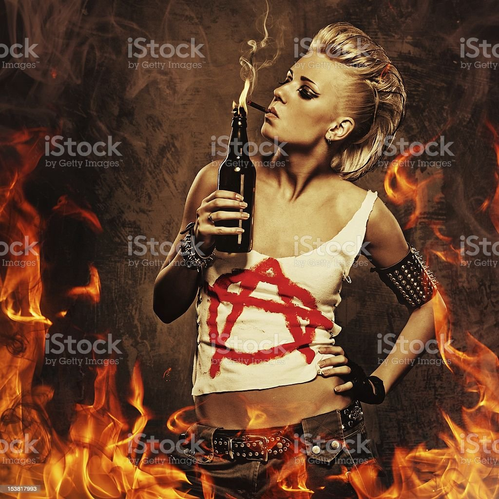 Punk girl smoking a cigarette over fire background. stock photo
