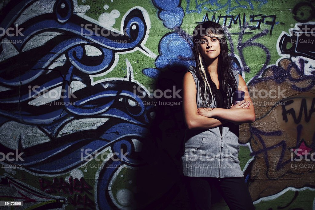 Punk Girl Standing in Front of Spray Painted Wall royalty-free stock photo
