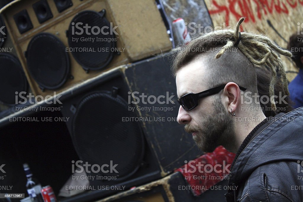 """Punk in sunglasses, Notting Hill Carnival """"London, England - August 29, 2011: A punk man calmly enjoys the roots reggae being blasted from one of the Notting Hill Carnival's sound systems. The carnival, which takes place in west London every August, attracts one million revellers to the city's streets."""" Adult Stock Photo"""