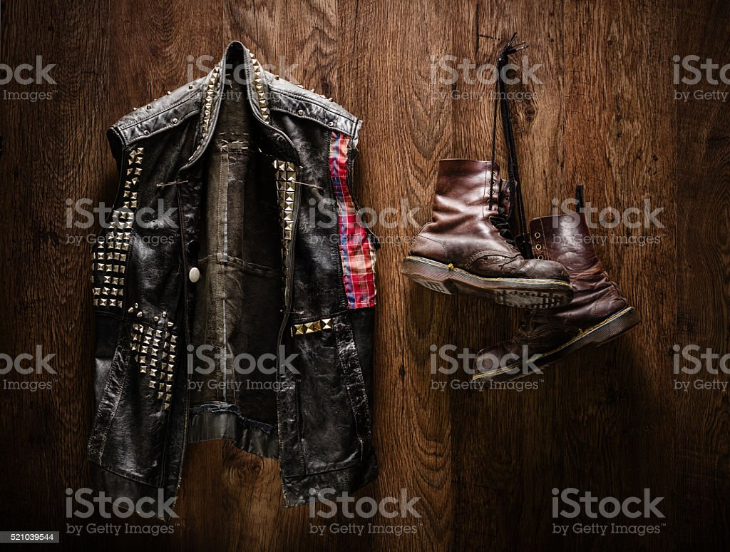 Punk jacket and boots hanging on a wall stock photo