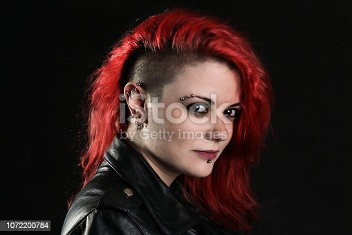 Unusual hairsyle and piercings on a punk woman. About 25 years old, Caucasian red head.