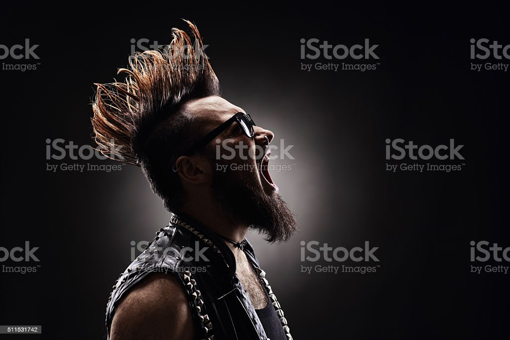Punk rocker shouting on dark background stock photo