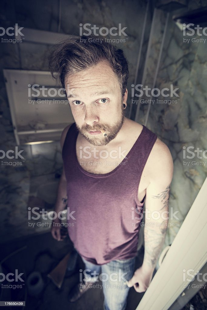 Punk rocker smokes cigarettes in dirty WC royalty-free stock photo