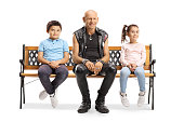 Punk sitting on a bench between a little boy and girl isolated on white background