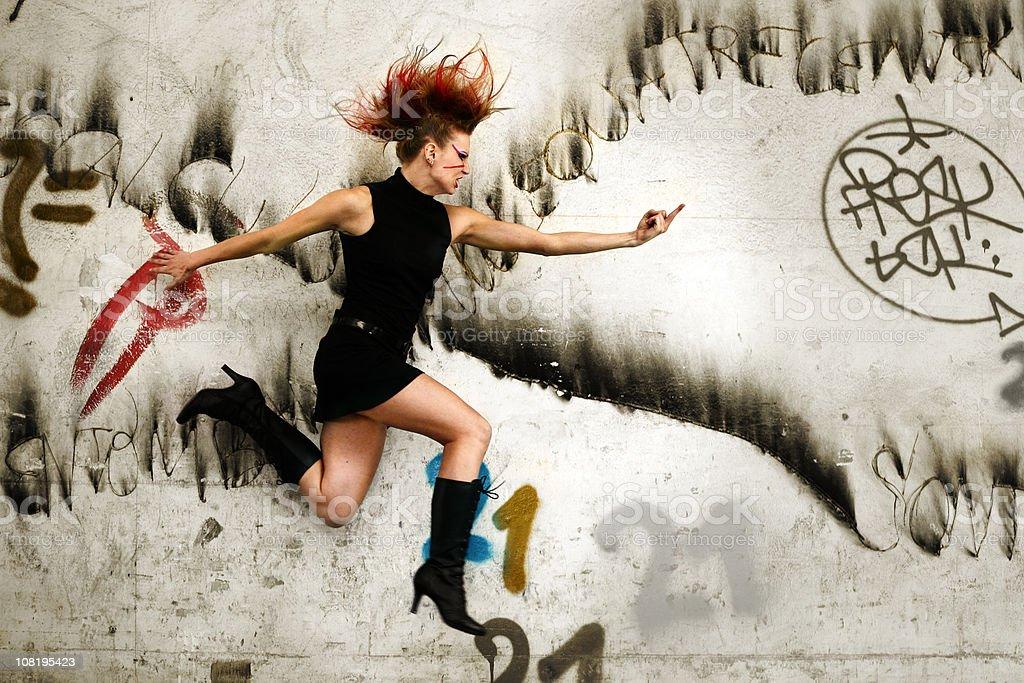 Punk Woman Jumping in Urban Area stock photo