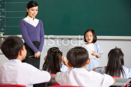 181085327 istock photo Pupil And Teacher Standing By Blackboard In Chinese School Classroom 177771947