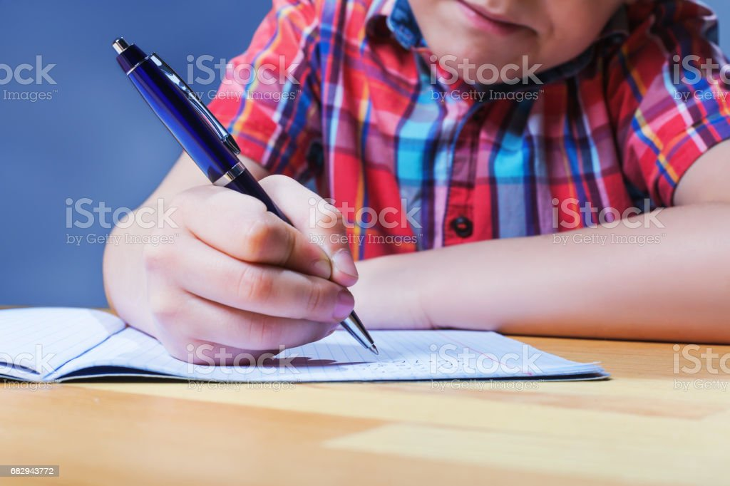 Pupil at the desk writing in notebook closeup view royalty-free stock photo