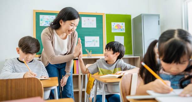 murid laki-laki hi lima dengan guru di kelas di sekolah dasar. anak siswa belajar di sekolah dasar. anak-anak menulis catatan di kelas. pengetahuan pendidikan, konsep kerja tim yang sukses - teaching in class potret stok, foto, & gambar bebas royalti